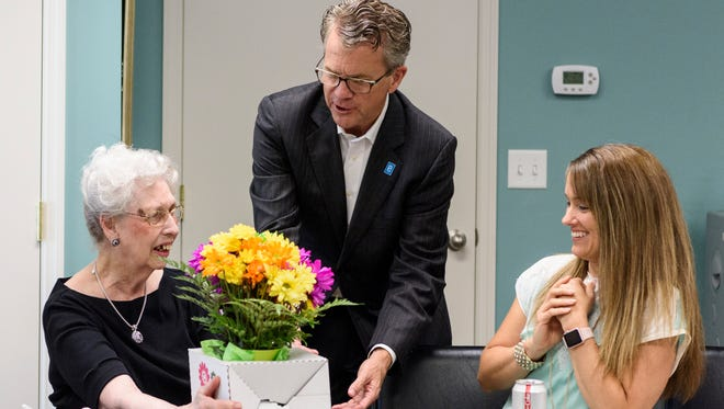 Mayor Lloyd Winnecke (center) delivers flowers to Doris Bedillion (left) as her co-worker Christie Hagan and others watch during a party celebrating Bedillion's 30-year work anniversary at the Lampion Center in Evansville, Ind., Wednesday, June 6, 2018. The 88-year-old serves as a full-time senior administrative assistant for the Lampion Center and has no plans to transition to part-time or retire in the near future.