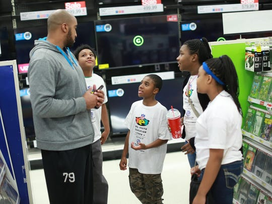 Lions defensive end Larry Webster listens to Christopher Kyles, 11, Delmarco Gantz, 10, Tiyanna Moore, 10, and Walden on Tuesday in Dearborn.