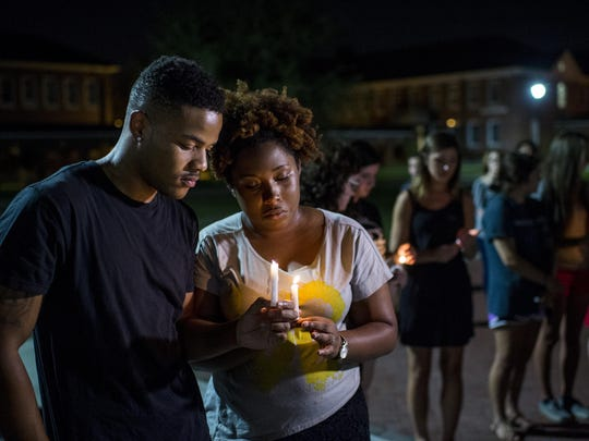 Sheldon Gilton, a UL-Lafayette business student, Brea Butler, a psychology student, pray during a candlelight vigil for the Grand 16 Theatre shooting victims Friday at the University of Louisiana at Lafayette in Lafayette. Two victims were killed with an additional nine wounded in a shooting at the movie theater on Thursday evening. The gunman also took his own life.