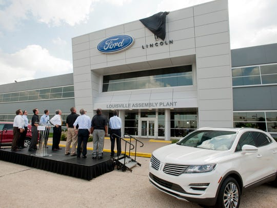 Company officials, UAW representatives and political leaders watch as the Lincoln logo is unveiled at the The Ford Motor Company's Louisville Assembly Plant, where its newest car, the Lincoln MKC, right, was introduced. 25 August 2014