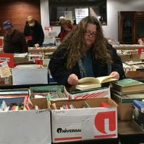"""Monica Young examines a book to decide if it interests her Saturday during the Friends of Morrisson-Reeves Library sale. She said she occasionally attends the Friends sales for the books and the prices. """"I have a huge collection,"""" she said."""