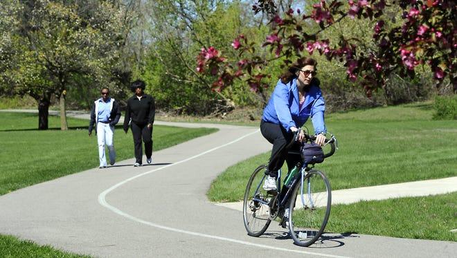 A bicyclist enjoys the River Trail near Potter Park Zoo.