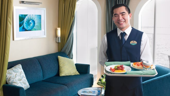 A steward delivers room service on a Royal Caribbean ship.