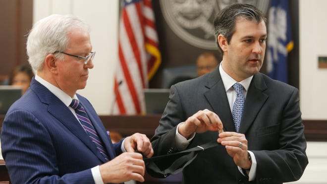 Defense attorney Andy Savage, left, helps hold an item for former North Charleston police officer Michael Slager as Slager testifies in his murder trial at the Charleston County court in Charleston, S.C., Tuesday, Nov. 29, 2016.