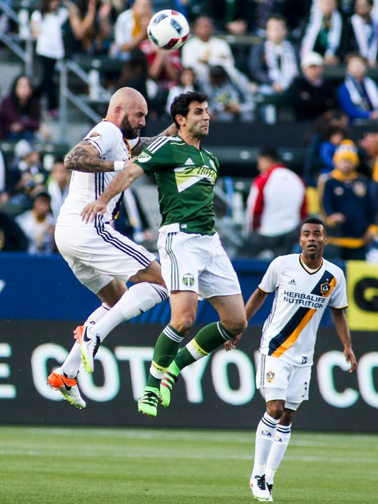 Portland Timbers midfielder Diego Valeri, center and Los Angeles Galaxy defender Jelle Van Damme jump up for a header during the first half of an MLS soccer game in Carson, Calif., Sunday April 10, 2016. (AP Photo/Ringo H.W. Chiu)