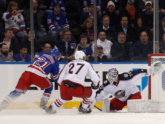 New York Rangers center Derek Stepan (21) tries to score behind Columbus Blue Jackets goalie Joonas Korpisalo as defenseman Ryan Murray (27) helps Korpisalo during the first period of an NHL hockey game, Tuesday, Jan. 31, 2017, in New York. (AP Photo/Julie Jacobson)