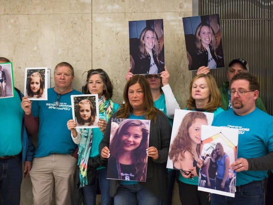 Parents of Larry Nassar victims hold up photos of their