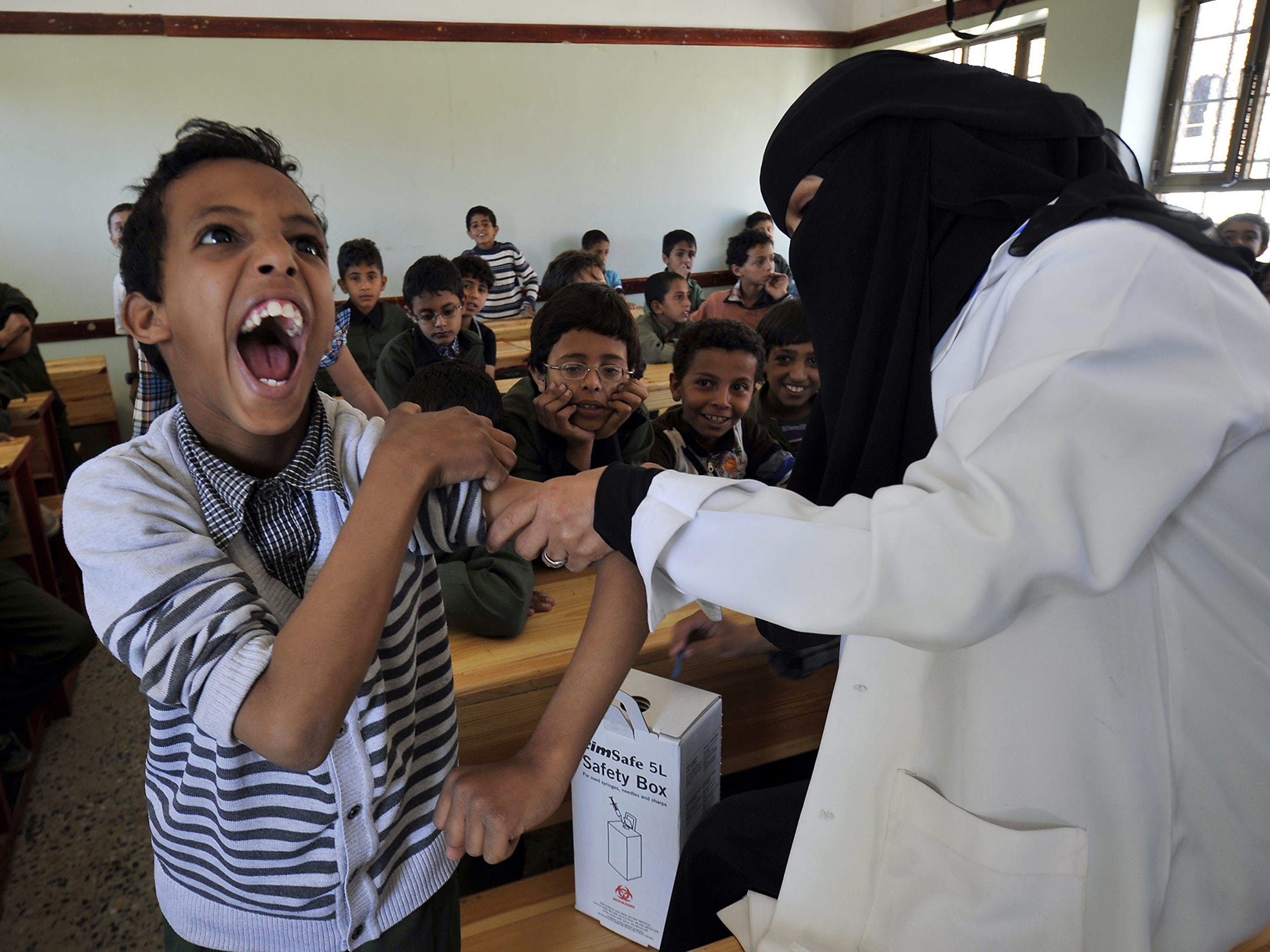 A student receives a measles vaccine on Nov. 11 in Sanaa, Yemen.