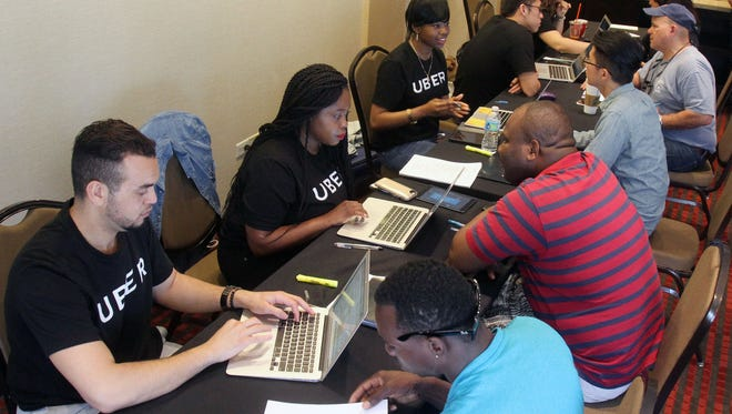 Uber representatives takes down information from prospective Uber drivers, during a Uber recruitment drive at the Hyatt Place Hotel in Yonkers May 17, 2017.