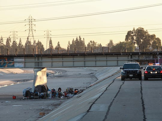 Police patrol near a homeless camp in the Los Angeles suburb of Downey in November.