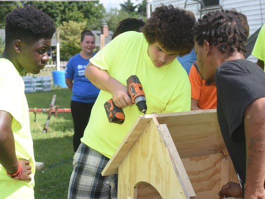 Malik Taylor, 13, of Salisbury, left, Ricardo Quillen, 13, of Salisbury and Joe Pindar of Salisbury screw thr roofing boards on one of the dog houses during The Young Lions Dog House build at Trinity Tabernacle Church and Comminity Center in Salisbury Sunday, Sept. 17, 2017. The youth group sponsored by Labyrinth 807 Masonic Lodge of Salisbury, were on their way to building 15 dog houses with donated material by Lowe's of Salisbury and The Roofing Center. (Photo by Todd Dudek for The Daily Times)