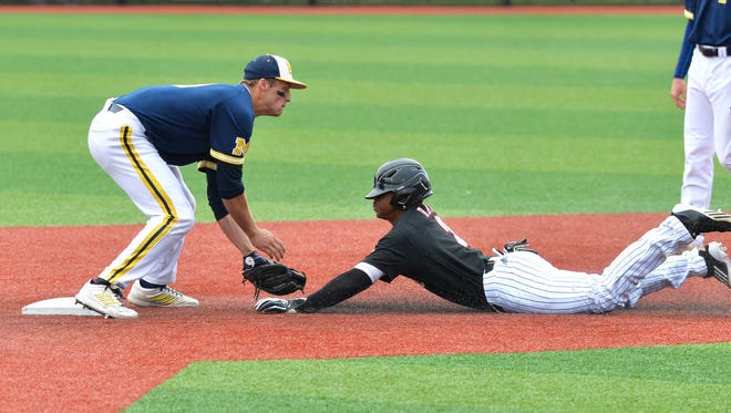 Louisville's Corey Ray, right, is tagged out by Michigan's Travis Maezes as he attempted to steal second during the fourth inning of an NCAA college baseball tournament regional game Sunday, May 31, 2015, in Louisville Ky.