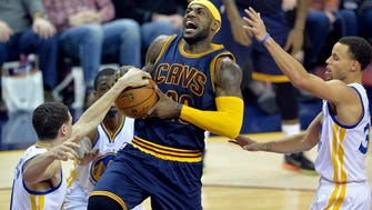 Feb 26, 2015; Cleveland, OH, USA; Cleveland Cavaliers forward LeBron James (23) drives between Golden State Warriors guard Klay Thompson (left) and guard Stephen Curry (30) in the third quarter at Quicken Loans Arena. Mandatory Credit: David Richard-USA TODAY Sports