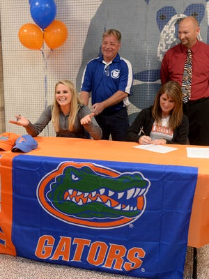 Brooke Madden, left, signs her national letter of intent Wednesday, Nov. 11, 2015, at Centerville High School to compete in diving for the University of Florida, a Division I program in Gainesville, Florida. Supporting Madden are diving coach Brad Whited, Principal Mike McCoy and mother Kim Moore.