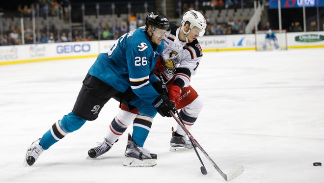The San Jose Barracuda's Buddy Robinson fights for the puck against the Grand Rapids Griffins' Evgeny Svechnikov in the third period Sunday night.
