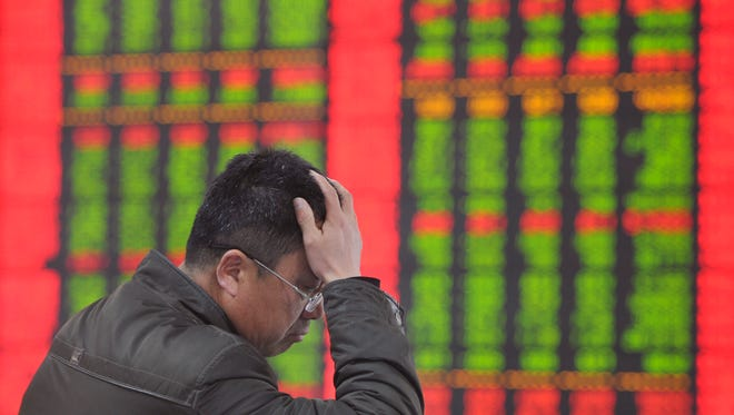 An investor holds his head as he monitors stock prices at a brokerage house in Fuyang in central China's Anhui province Monday, Jan. 19, 2015.