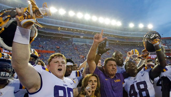 LSU wide receiver Jonathan Giles (89) and linebacker Donnie Alexander (48) celebrate victory over Florida 17-16 with LSU head coach Ed Orgeron, second from right, and his wife Kelly Oregon after an NCAA college football game, Saturday, Oct. 7, 2017, in Gainesville, Fla.