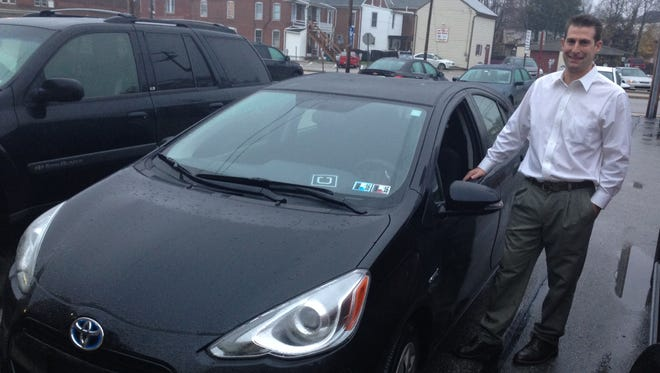 Paul Arigo stands with his new Prius as a certified Uber driver on Dec. 2, 2015
