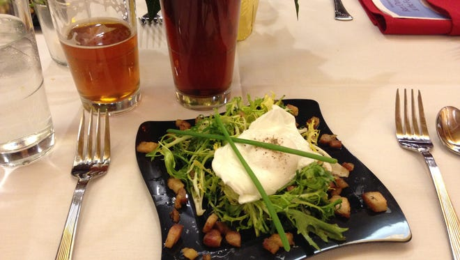 A frisee salad prepared with prosciutto, bacon lardon and a poached egg.