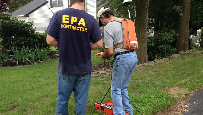 EPA contractors Kyle Harmish (left) and John Williams use ground-penetrating machines to do preliminary sweeps of properties near Birchly Court, in 2016. A more extensive cleanup is planned for the area, where crushed car batteries were found to be buried.