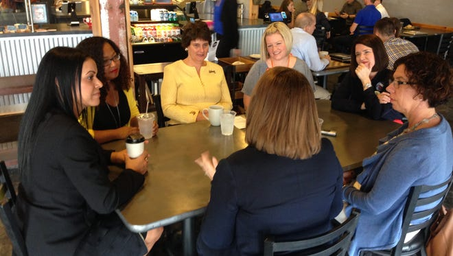 Anne Holton, wife of Democratic vice presidential candidate Tim Kaine, meets with a group of community activists Wednesday at the Red Cedar Cafe in East Lansing. Holton is seated in the center, wearing yellow.