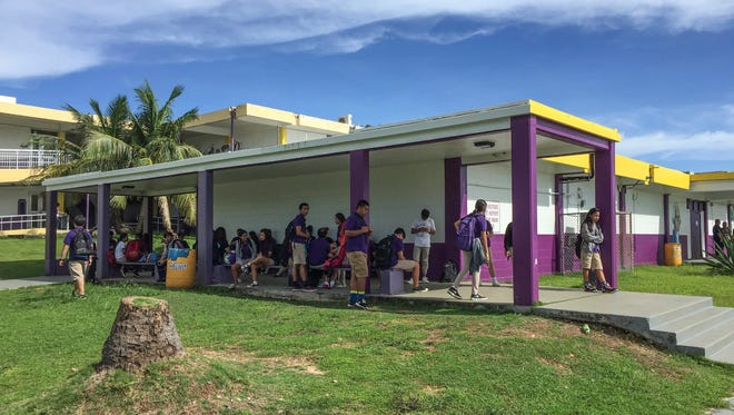 A group of George Washington High School students waits for a ride home from the Mangilao campus on Nov. 10, 2016.