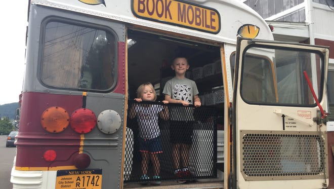Isabelle Earl, 2, and Peyton Earl, 5, both of Endwell, hang out at the Johnson City Book Mobile.