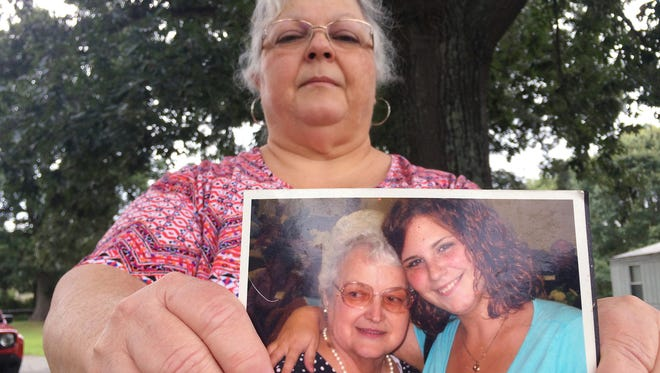 Susan Bro, the mother of Heather Heyer, holds a photo of Bro's mother and her daughter, Monday, Aug. 14, 2017, in Charlottesville, Va.