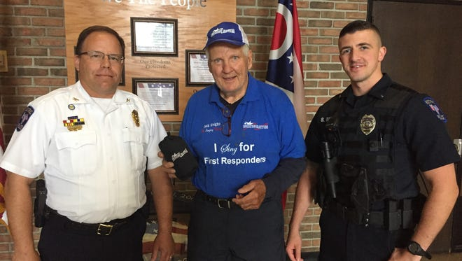 """Bucyrus Police Chief David Koepke, left, and Officer Scott Davis, right, stand with Jack Knight, """"The Singing Patriot."""""""