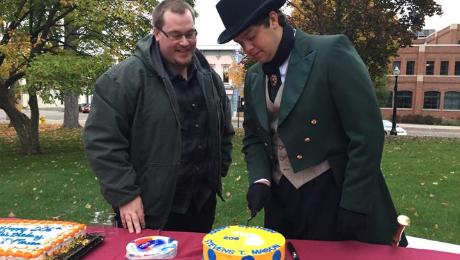 State House candidate Alec Findlay, left, and Okemos High School student Braden Cooley, portraying former Michigan Gov. Stevens T. Mason, cut a birthday cake for Mason at Findlay's campaign kickoff rally at the Ingham County courthouse in Mason on Friday, Oct. 27, 2017.