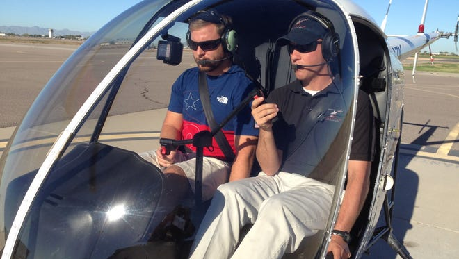 Patrick Zahm (left) and instructor Jeff Thomasson prepping an R22 Helicopter for takeoff. Both are former Marines and participants in the CGCC Veteran's flight training program.
