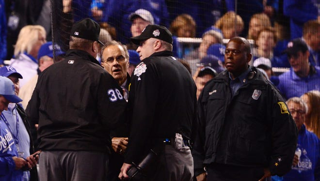 MLB chief baseball officer Joe Torre talks with the umpires as the FOX broadcast goes out in the fourth inning.