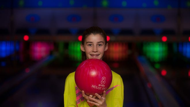 Kayleigh Armstrong, age 9m posses for a photo near the new neon bowling lanes at the new renovated Cherry Hill Playdrome in Cherry Hill. The Big Event offers a new VIP bowling section and a Game Mania arcade room.
