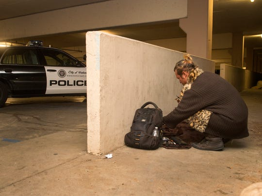 William Bennett, 31, of Ventura, packs up his belongings after police found him sleeping  along the Ventura Promenade in November. Officers cited and released Bennett on suspicion of drug possession.
