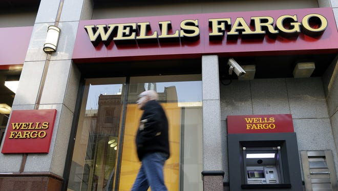 In this Wednesday, Dec. 19, 2012, file photo, a man walks past a Wells Fargo branch in Philadelphia.
