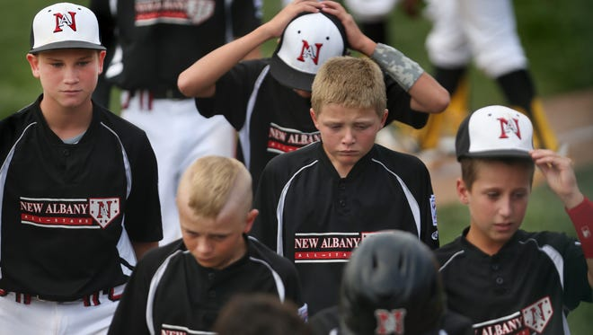 Dejected New Albany, Ind. Little Leaguers leave the field after giving up a 5-0 lead, only to lost 12-7 to the Jackie Robinson West Little Leaguers from Chicago in the Little league Baseball Central Regional Championship at the Ruben F. Glick Little League Baseball Center in Lawrence, Ind. on Saturday, August 9, 2014. The defining blow was a 2-out grand slam by JRW's Can Bufford in the top of the fifth inning that put his team ahead 10-7.