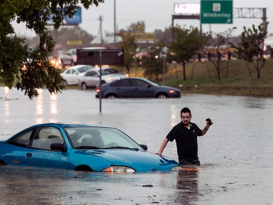 Mike Stoner gets out of his flooded car, Friday, Oct. 30, 2015 in San Marcos, Texas. A fast-moving storm packing heavy rain and destructive winds overwhelmed rivers and prompted evacuations Friday in the same area of Central Texas that saw devastating spring floods. (Rodolfo Gonzalez/Austin American-Statesman via AP)  AUSTIN CHRONICLE OUT, COMMUNITY IMPACT OUT, INTERNET AND TV MUST CREDIT PHOTOGRAPHER AND STATESMAN.COM, MAGS OUT; MANDATORY CREDIT