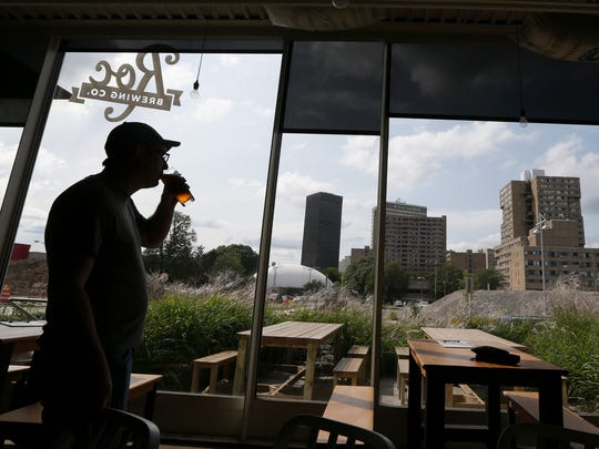 Chris Spinelli, co-owner, Roc Brewing Co, takes a break for a sip of one of his beers on tap inside his brewery along S. Union Street in downtown Rochester.
