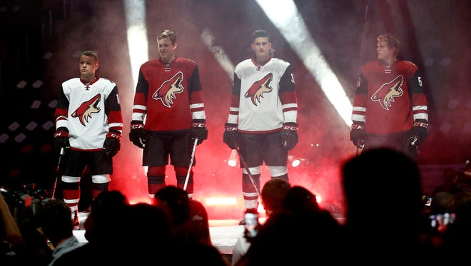 Arizona Coyotes (from left) Max Domi, Connor Murphy, Brendan Perlini and Christian Dvorak show off the team's new uniforms during the Coyotes draft party on Friday, June 26, 2015, at Gila River Arena in Glendale.