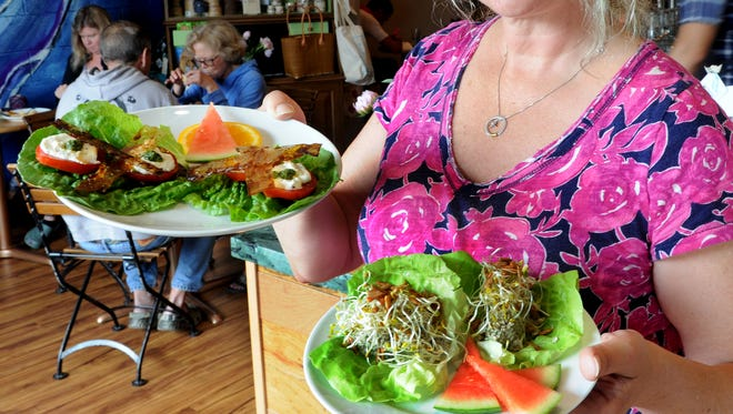 Christine Burke, owner of Ambrosia by Caffrodite, displays the Saturn BLT + C and Supernova Sunflower Seed Ship.