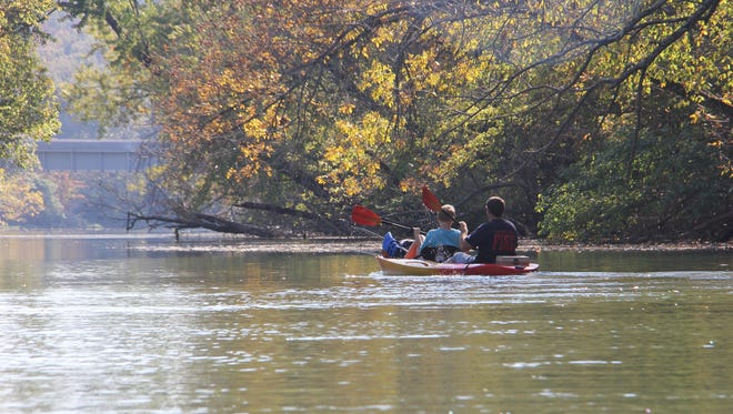 Tandem kayakers enjoy a stretch fall colors along the James River Water Trail northeast of Lake Springfield. Jason Bogema, with son Noah in front, paddles a quiet stretch of the James River Water Trail on a sunny fall afternoon last week.  Wes Johnson/News-Leader