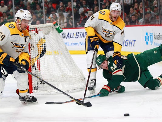 Minnesota Wild's Mikael Granlund (64), of Finland, is taken down by Nashville Predators Mattias Ekholm (14), of Sweden, and Predators Roman Josi (59), of Switzerland, during the first period of an NHL hockey game on Friday, Dec. 29, 2017, in St. Paul, Minn. (AP Photo/Andy Clayton-King)