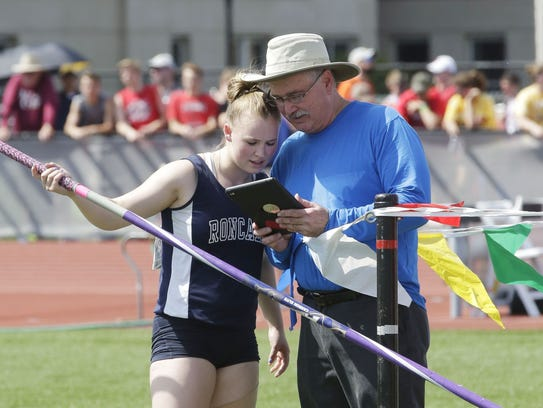 Manitowoc Roncalli coach Don Penza shows Kelly Jacoby her pole vault he recorded on his tablet during last year's WIAA state track and field meet.