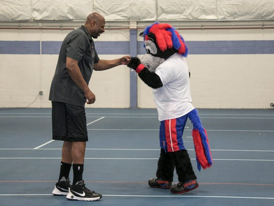 Pistons legend Earl Cureton fist-bumps Pistons mascot Hooper at The Detroit Pistons hold a Pistons Fit Clinic with Henry Ford Health System program at the Redford Service Leaning Academy, winner of the inaugural Pistons Fit School Challenge Clinic Friday, June 1, 2018 in Redford Township.