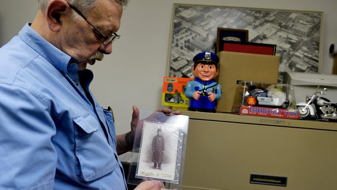 Police Heritage Museum founder John Stine shows an old photograph of a York City police officer in a back room in the museum in York on Thursday, May 7, 2015. The museum has about 2,000 photographs that are not on display. The museum, which was founded in 1995, is looking for a new location after finalizing a deal to sell its West Market Street building to Royal Square Development. Operated as a non-profit, the museum displays many artifacts with York County origins, as well as items from across the nation and other countries. Chris Dunn -- Daily Record/Sunday News