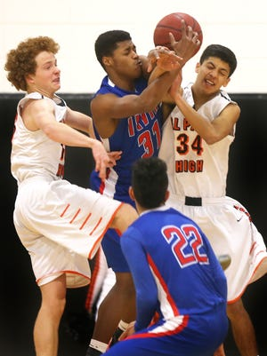 Irvin's Daaron Saleem, top center, fought for a rebound with El Paso High's Michael Lynch, left, and Zach Roberson during the third quarter Saturday at El Paso High School.