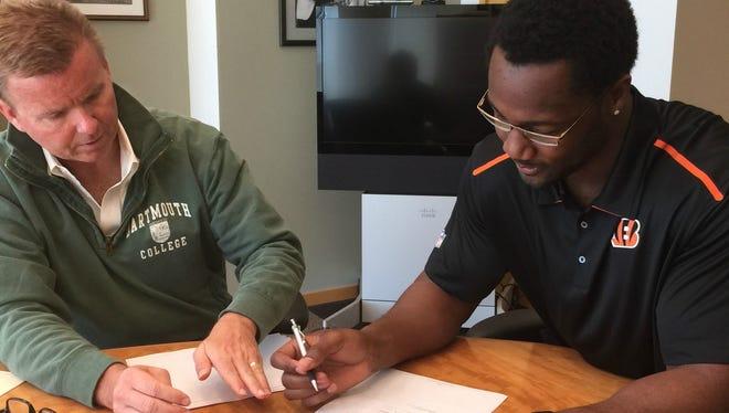 Michael Johnson signs his Bengals contract alongside team VP Troy Blackburn.