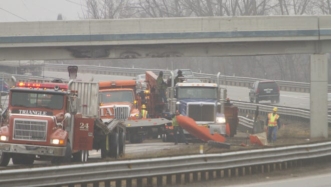 In this file photo from March 2016, workers remove debris from a truck that hit the Eight Mile overpass at northbound U.S. 23 in Green Oak Township.