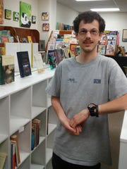 Store employee Kevin Gossen poses inside Other Worlds Books & More in Sturgeon Bay.