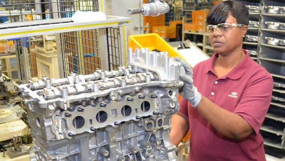 Hyundai worker Rite Edwards installs a timing chain